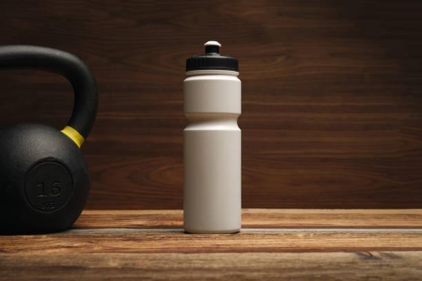 equipo de fitness y suplementos en suelo de madera en el gimnasio gimnasio de fondo con batidor de botellades de agua y kettlebell espacio de copia libre - set deportivo fotografías e imágenes de stock