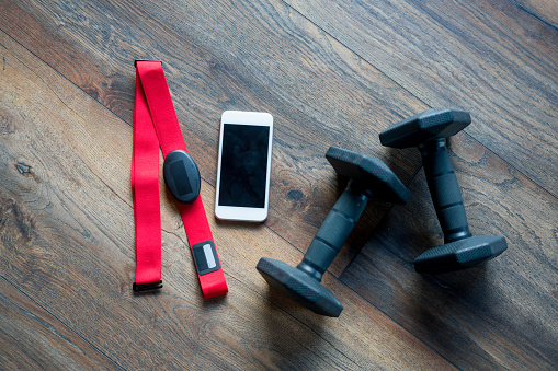 Fitness equipment for a good workout lying on the floor at the gym - fitness tracker and weights