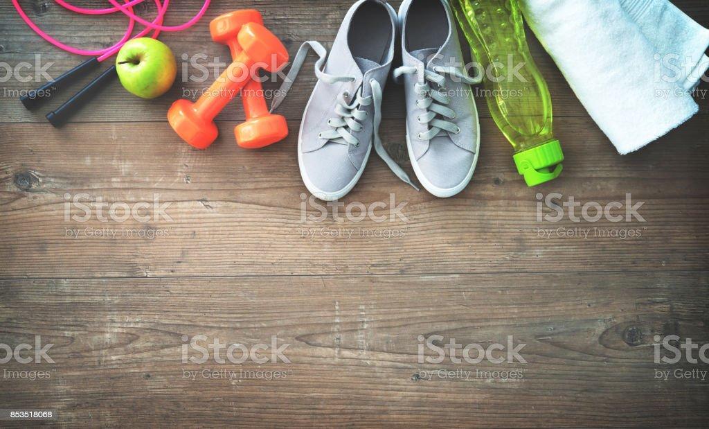 Fitnessgeräte, gesunde Ernährung, Turnschuhe, Wasserflasche und Handtuch – Foto
