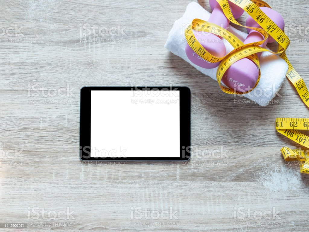 Fitness equipment with dumbbells, towel and digital tablet blank...