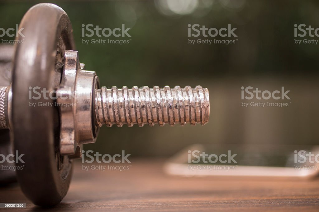 Fitness, exercise themed scene with barbell and smart phone. royalty-free stock photo