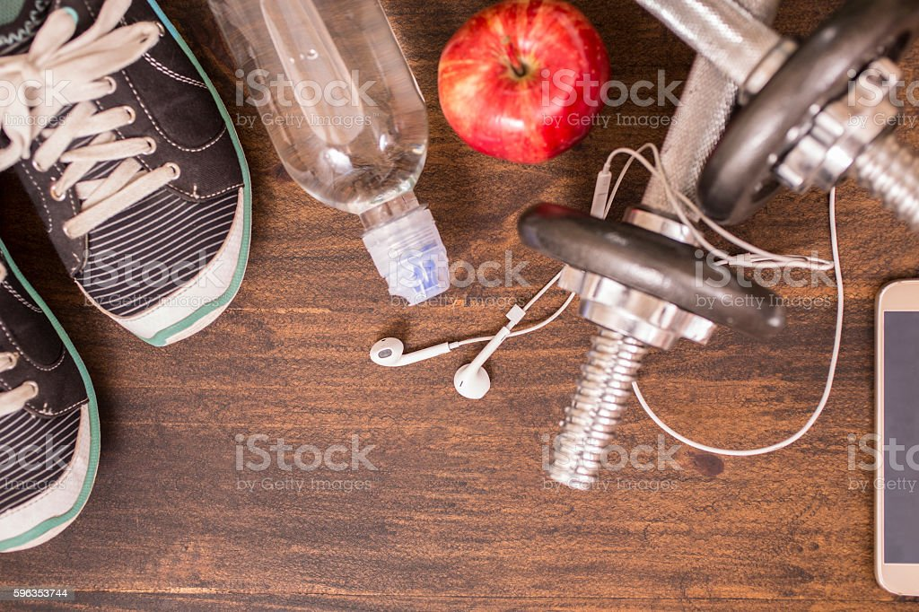 Fitness, exercise themed scene with barbells, sneakers, earbuds. royalty-free stock photo