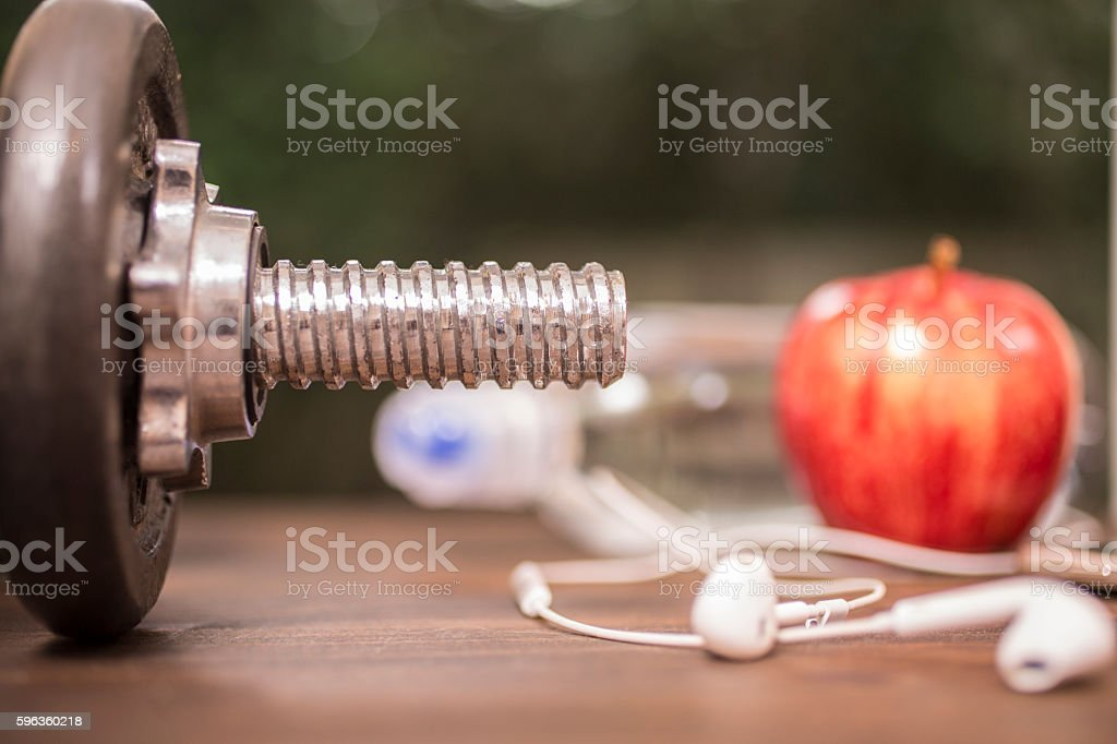 Fitness, exercise themed scene with weights, earbuds, apple. royalty-free stock photo
