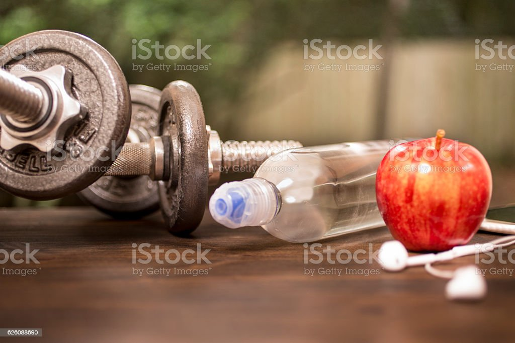 Fitness, exercise themed scene with weights, earbuds, apple. stock photo