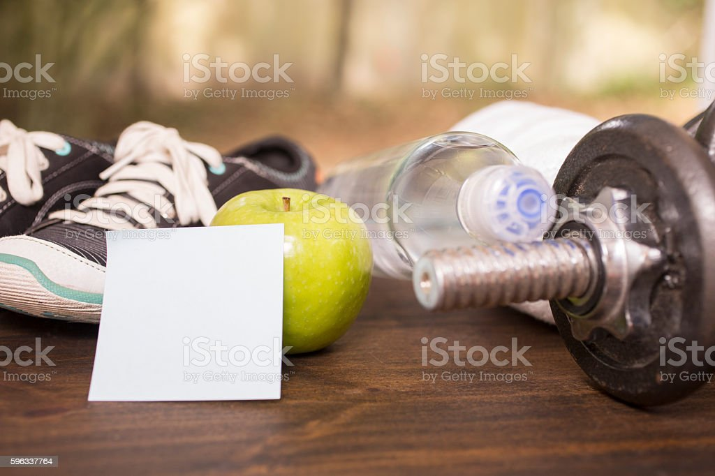 Fitness, exercise themed scene with weights, sneakers, apple. royalty-free stock photo