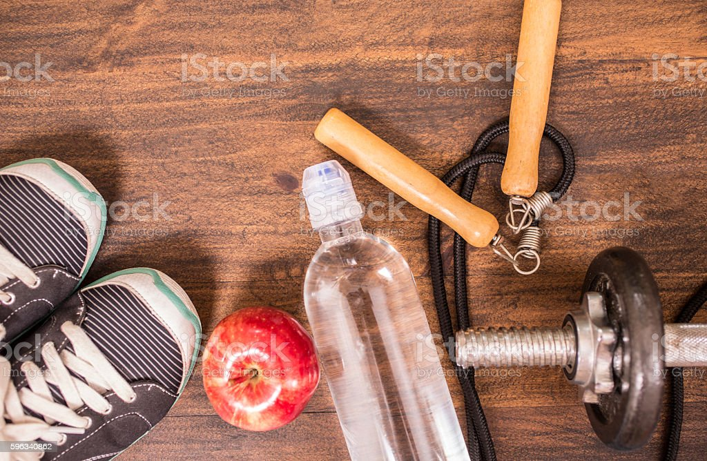 Fitness, exercise themed scene with weights, sneakers, apple. Lizenzfreies stock-foto