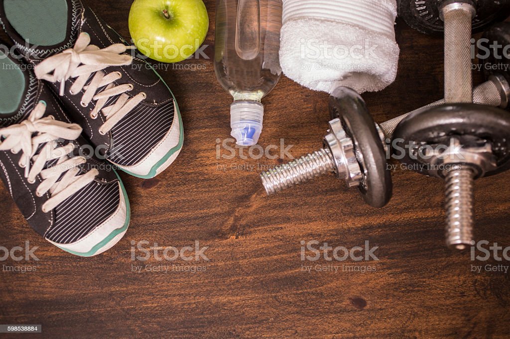 Fitness, exercise themed scene with weights, sneakers, apple. photo libre de droits