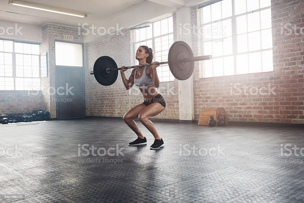 Fitness female athlete lifting weights in gym - Photo