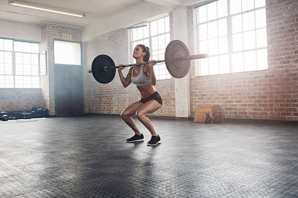 Fitness female athlete lifting weights in gym stock photo