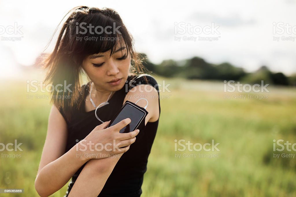 Fitness female checking her performance on smartphone royalty-free stock photo