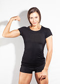 attractive muscular sporty woman showing her biceps in blank black t-shirt  isolated on white background