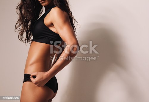 Close-up image of fitness female model in sportswear. Fit young woman with muscular body.