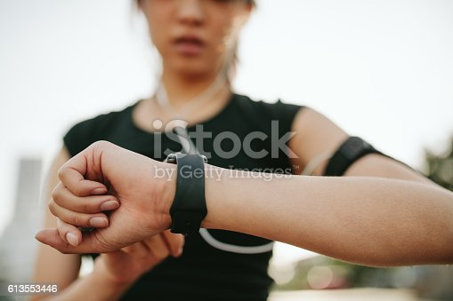 Close up shot of young sportswoman using smartwatch to track her workout performance. Fitness female monitoring her progress on smartwatch.