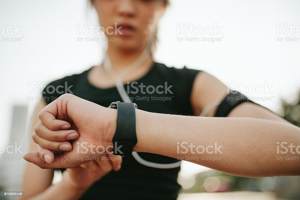 Fitness female monitoring her performance on smartwatch stock photo