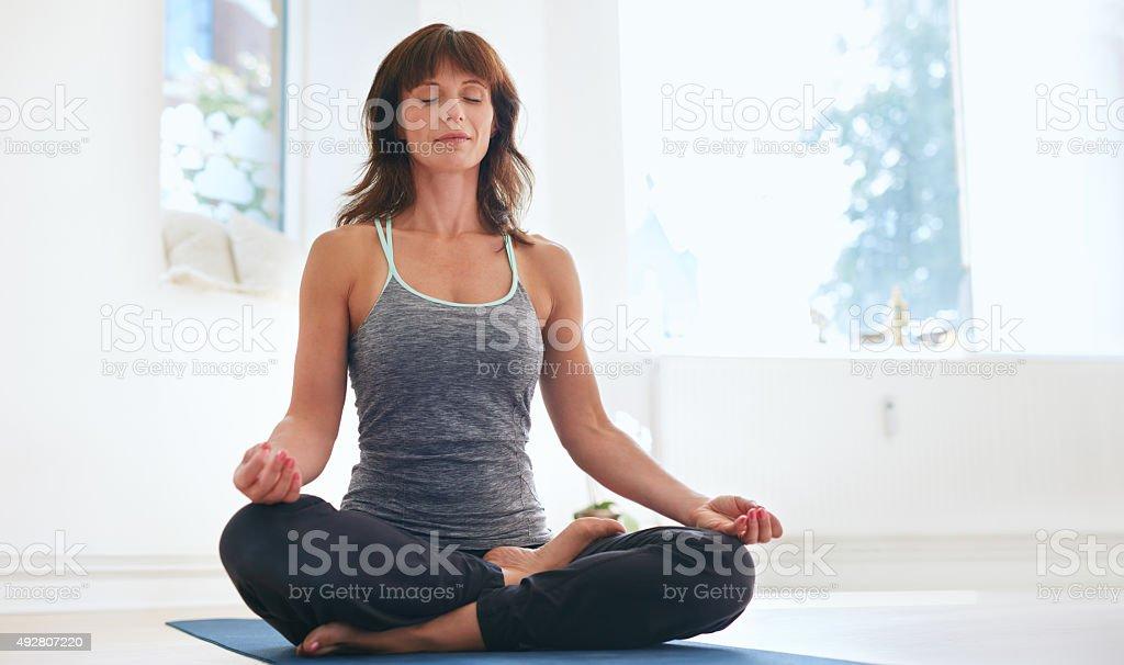 Fitness female practicing Padmasana at gym stock photo