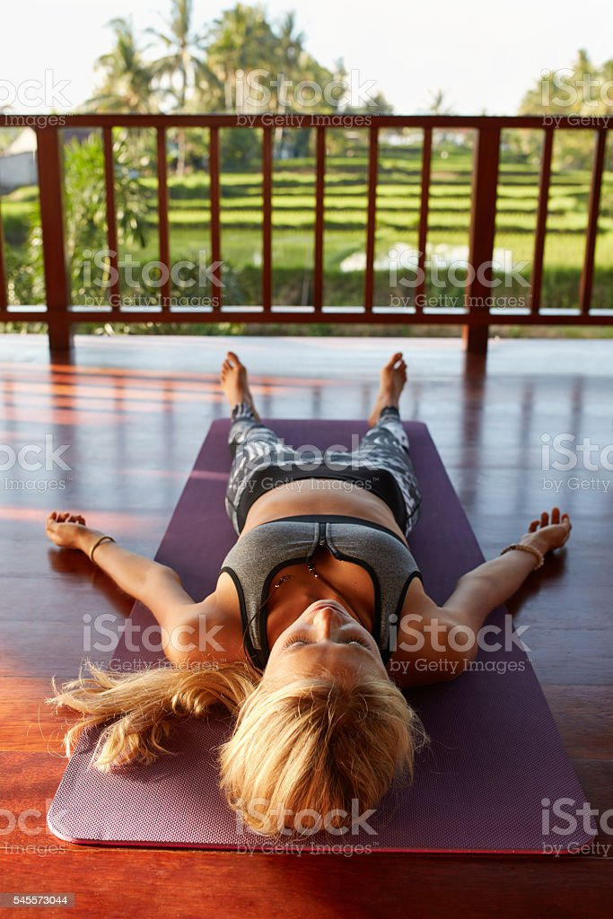 Fitness female relaxing in the Corpse pose stock photo