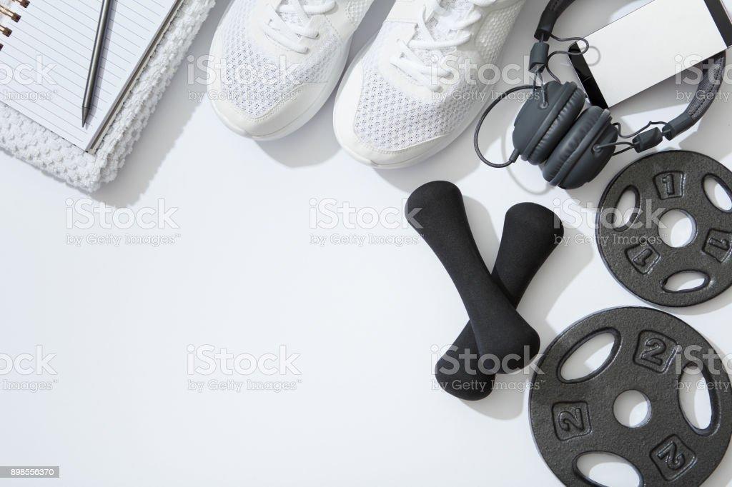 Fitness flat lay, dumbbells, notebook, headphones, notebook, towel on white background - Zbiór zdjęć royalty-free (Akcesorium osobiste)