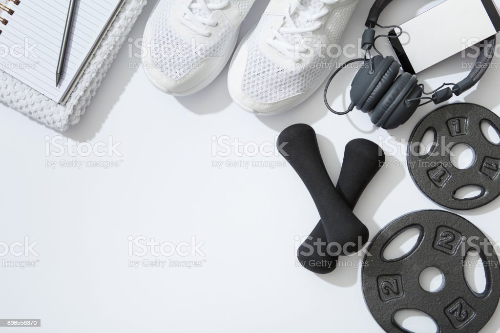 Fitness flat lay, dumbbells, notebook, headphones, notebook, towel on white background stock photo