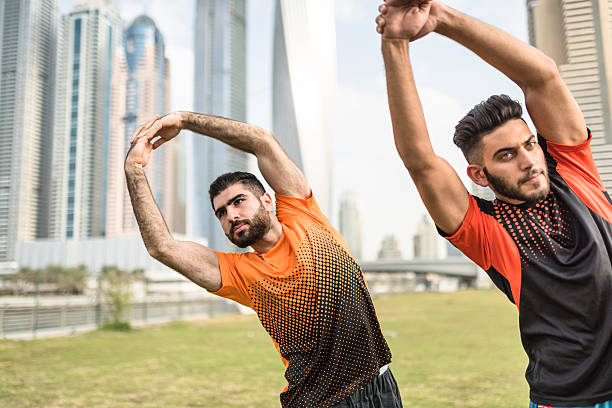 fitness friends doing stretching in dubai marina - human limb stock photos and pictures