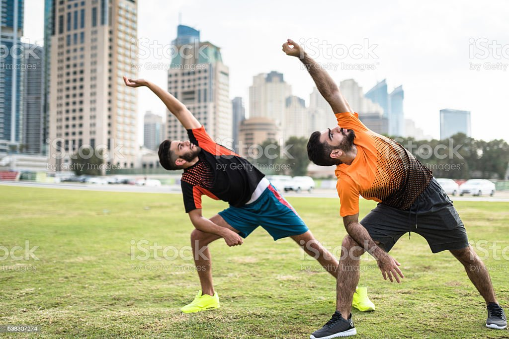 fitness friends doing stretching in dubai marina stock photo