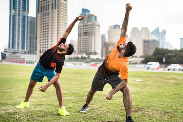 fitness friends doing stretching in dubai marina - foto de stock