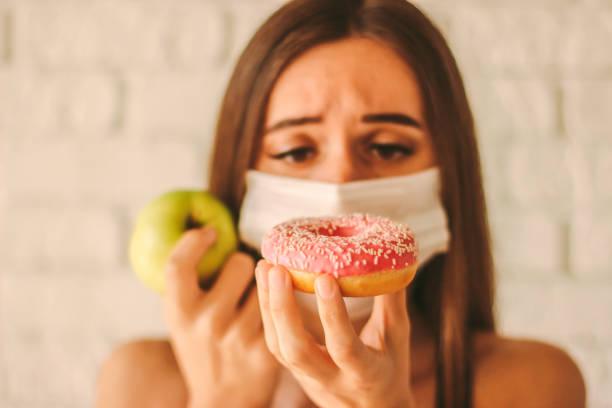 het meisje dat van de geschiktheid tussen gezonde appel en donut kiest - lichaamsbewustzijn stockfoto's en -beelden