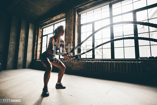 Fitness girl exercising with battle ropes at gym. Woman training doing battling rope workout working out arms and cardio for exercises.