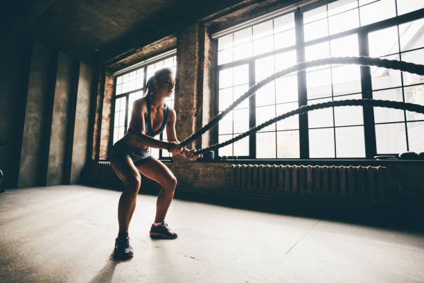 Fitness girl exercising with battle ropes at gym stock photo
