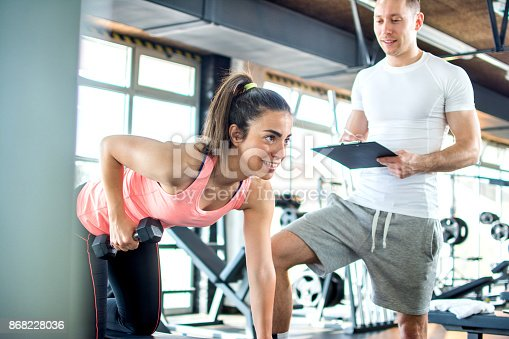 istock Fitness girl having weight training with assistance of coach in gym. 868228036