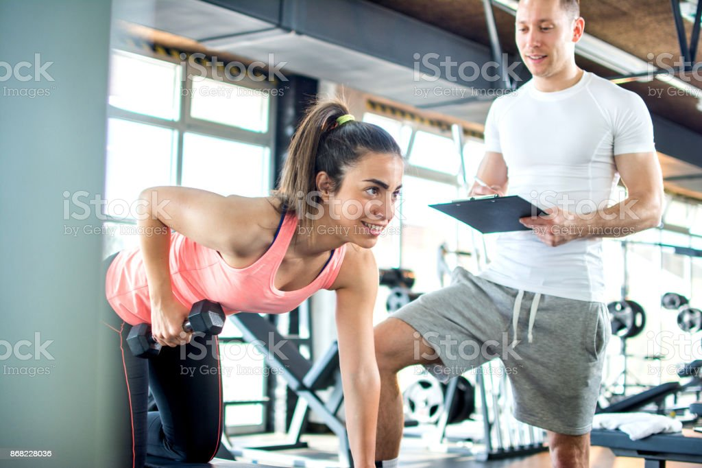 Fitness girl having weight training with assistance of coach in gym. stock photo