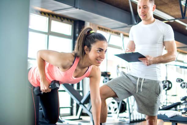 chica fitness con pesas con la ayuda del entrenador en el gimnasio. - entrenador personal fotografías e imágenes de stock