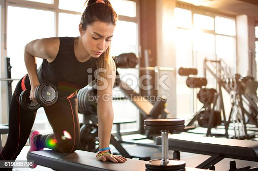 istock Fitness girl lifting dumbbell in the morning. 619088796