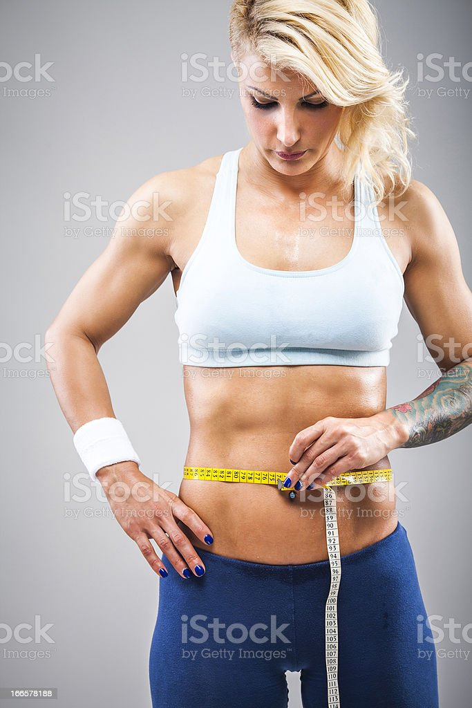Fitness girl measuring her waist royalty-free stock photo