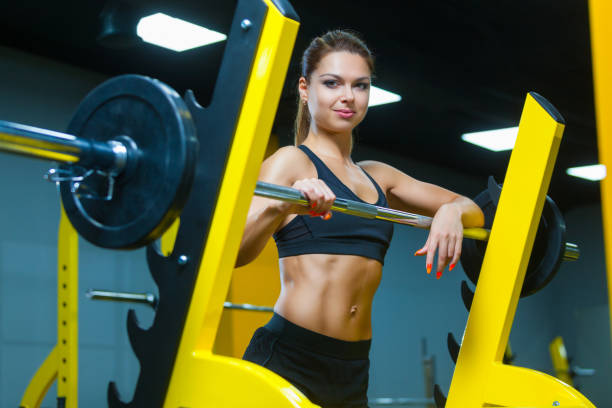 Fitness girl posing near the barbell in a modern gym. Muscles woman showing sixpack abs stock photo