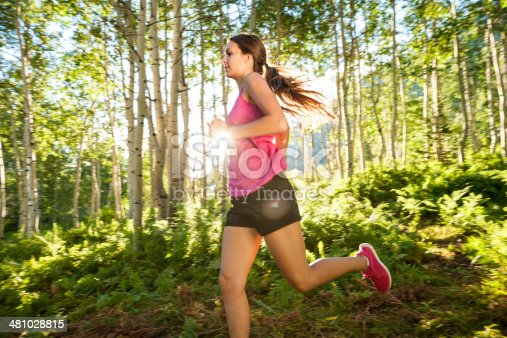 Action photograph of an attractive young woman running in a wooded glade of aspens and ferns, and enjoying the great outdoors as the sun sets in the background.