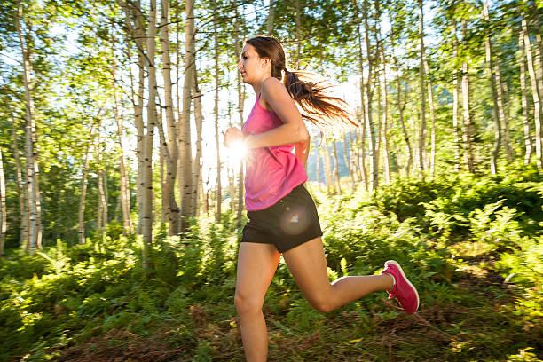 Fitness Girl Running in Aspen Grove at Sunset stock photo