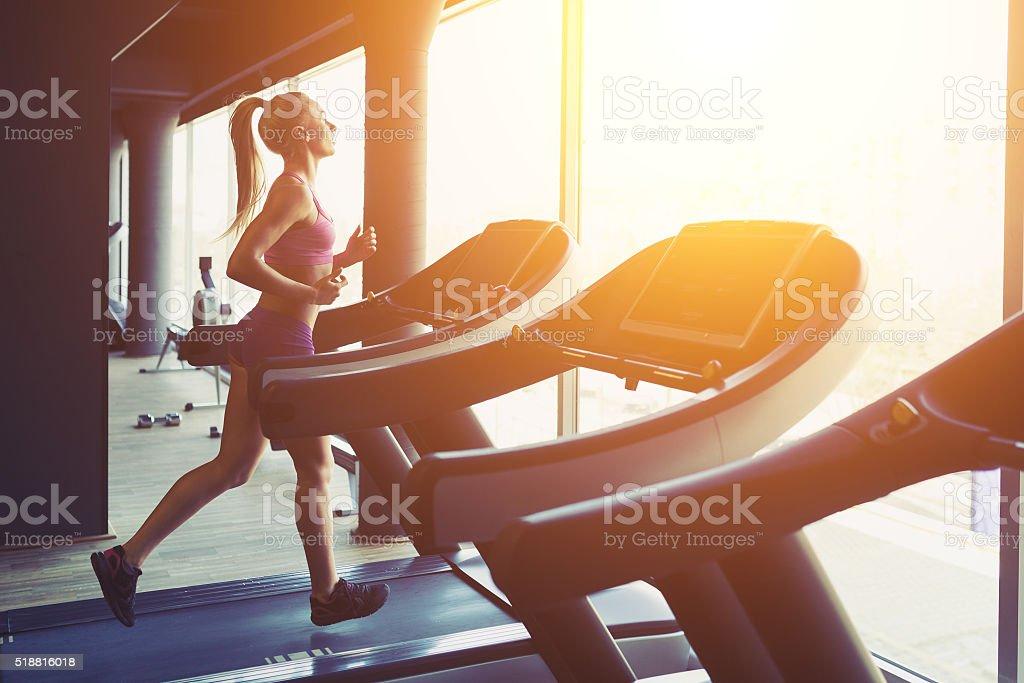 Fitness ragazza corre su un tapis roulant - foto stock