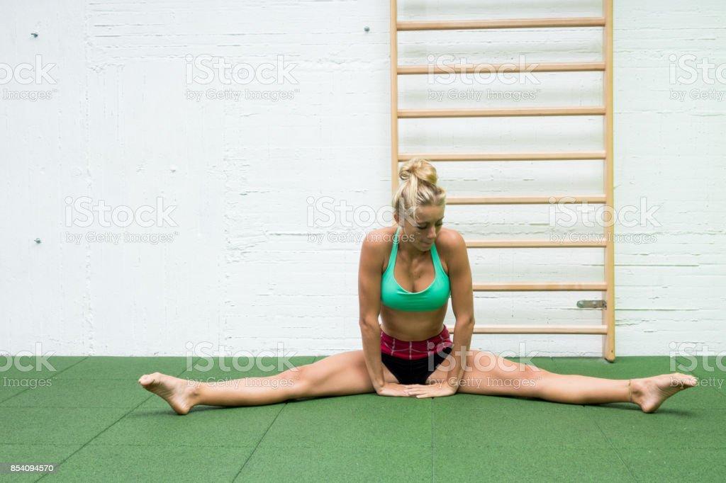 d6dbb07ed Haciendo pierna de pilates de estiramientos piernas fitness chica estira  ejercicios en gimnasio. Atleta ejercitar