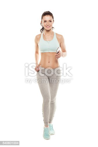 629605142istockphoto fitness girl with a smartphone on a white background 540601004