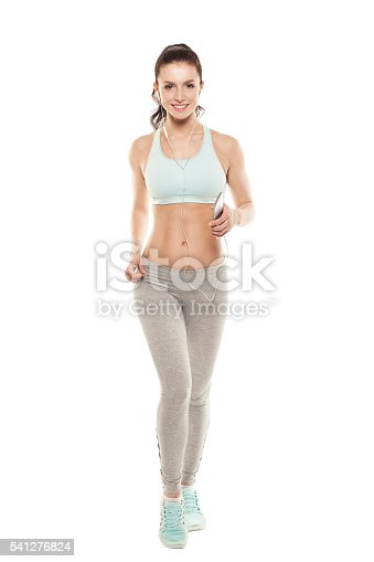 629605142istockphoto fitness girl with a smartphone on a white background 541276824