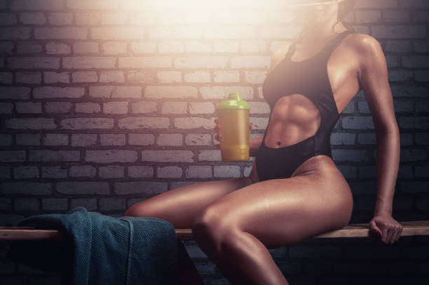Fitness girl with athletic body taking a break after core strength training in the gym. stock photo