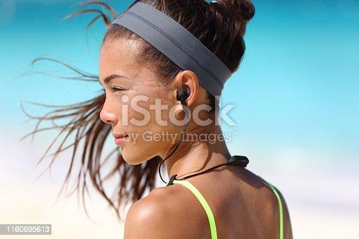 istock Fitness girl with sport in-ear wireless headphones 1160695613