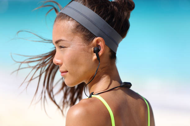 Fitness girl with sport in-ear wireless headphones Fitness girl with sport in-ear wireless headphones. Asian female athlete woman runner wearing Bluetooth earphones with wing tip design for sports activities. Portrait closeup. bluetooth stock pictures, royalty-free photos & images