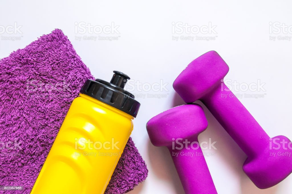 Fitness gym equipment. Dumbbells with towel and wate bottler. Workout footwear. Sport trainers on white background. sport, healthy lifestyle and objects concept stock photo