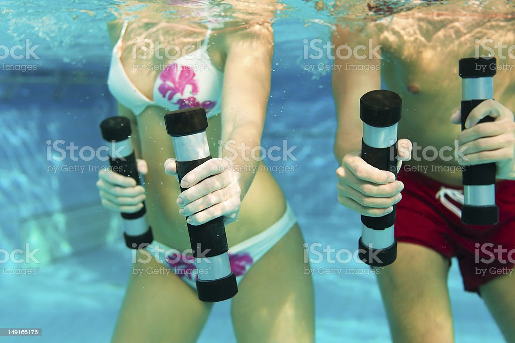 Fitness - gymnastics under water in swimming pool stock photo