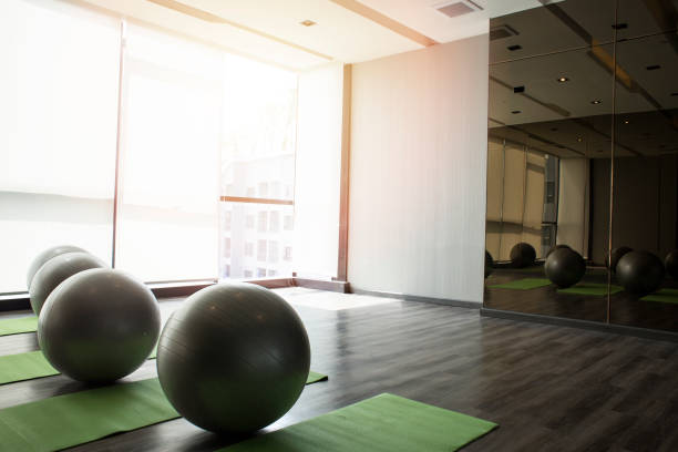 Fitness hall with sport equipment interior of gym with yoga Fitness hall with sport equipment interior of gym with yoga yoga studio stock pictures, royalty-free photos & images