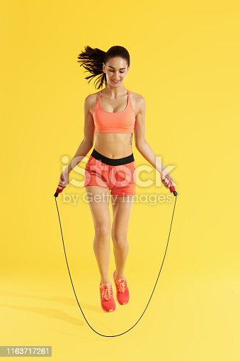 Fitness. Happy woman doing jumping exercises with skipping rope on colorful yellow background. Full length shot of smiling girl model with fit body doing cardio workout at studio
