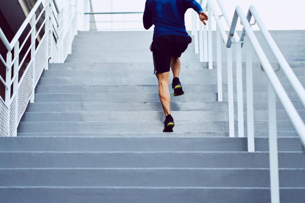 Fitness, health, and sport concept. Athletic man running upstairs stock photo