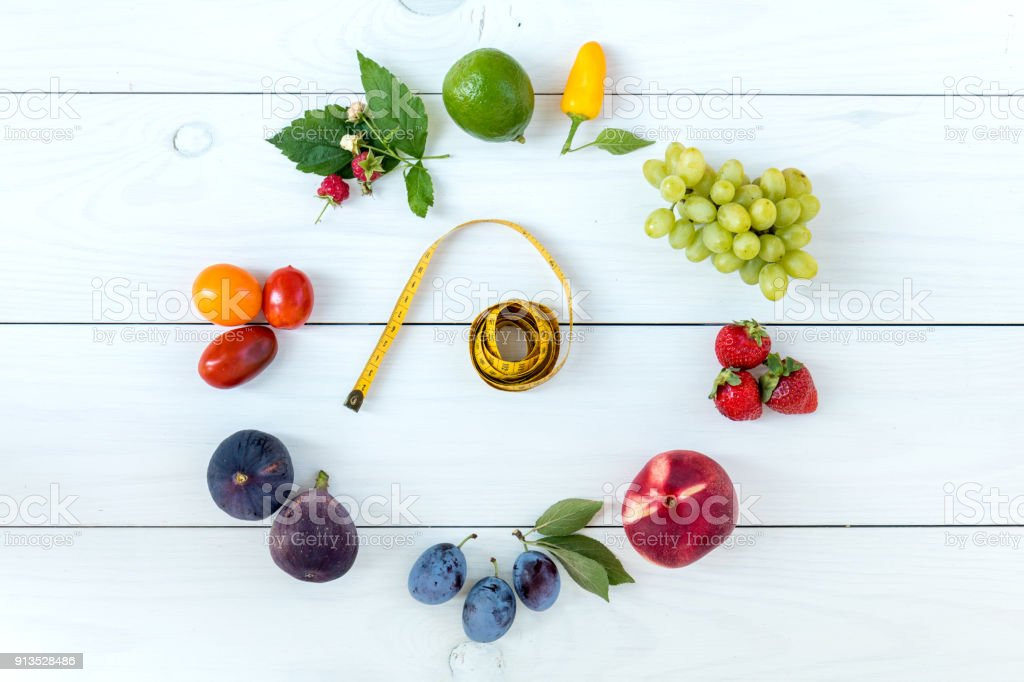 Fitness healthy food on white wooden background (lime, strawberry, plum, figs, raspberries, grapes, peppers, peaches, tomatoes nectarines and measuring tape) royalty-free stock photo
