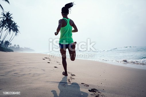174919648istockphoto Fitness healthy lifestyle young woman running on tropical beach during sunrise in the morning 1080206492